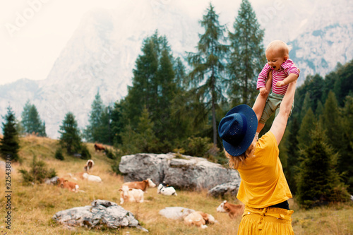 Back of a mother outside in nature lifting up her happy baby in front of a mountain meadow with cows - 325438870