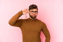 Young Caucasian Man Isolated On Pink Background Showing Thumb Down, Disappointment Concept.