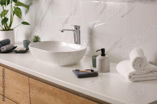 Fotografija Toiletries and stylish vessel sink on light countertop in modern bathroom