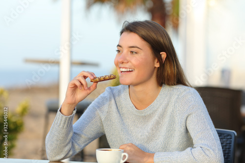 Happy girl eating a snack in a cafe terrace Fototapet
