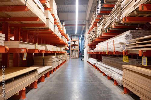 Hardware store. Shop of building materials. Racks with boards, wood and building material. loaded cart in a hardware store