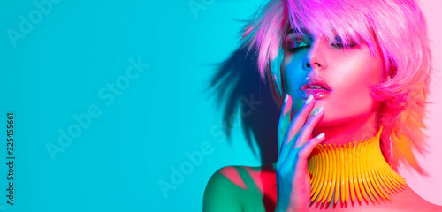 Fototapeta Fashion model woman in colorful bright lights, portrait of beautiful party girl with trendy make-up, manicure and haircut. Art design of disco dancer, colorful make up. Over colourful vivid background obraz