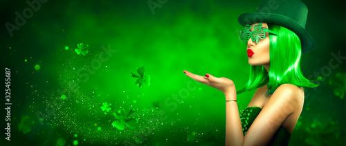 Obraz St. Patrick's Day leprechaun model girl pointing hand, holding product on green magic background, blowing flying shamrock leaves. Patrick Day pub party, celebrating. Border art design, Widescreen - fototapety do salonu