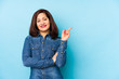canvas print picture - Middle age latin woman isolated on a blue background smiling cheerfully pointing with forefinger away.