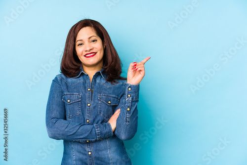Fototapeta Middle age latin woman isolated on a blue background smiling cheerfully pointing with forefinger away. obraz