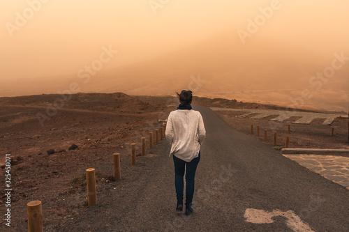 Photo Una mujer camina por un camino solitario en medio de una tormenta de arena
