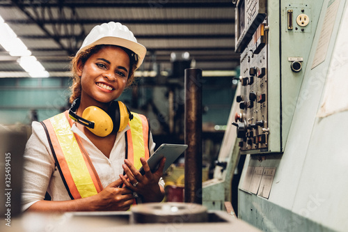 Fotografie, Tablou Industry maintenance engineer woman dark skin wearing uniform and safety helmet under inspection and checking production process on factory station by tablet