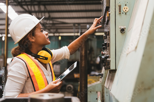 Fotografía Industrial factory maintenance engineers woman inspect relay protection system of machinery and holding digital tablet with copy space