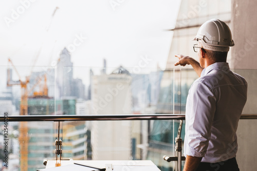 Fototapeta Portrait engineer man wearing safety helmet standing back and looking to the construction site with modern city background. Industry, Engineering, construction concept. With copy space for your text. obraz