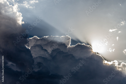 Fotografie, Tablou Clouds and Light. Sunlight backlights clouds with blue sky.