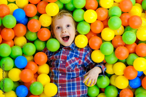 Obraz Happy child, kid boy playing, having fun on playground with colorful plastic balls in pool. Game center for family weekend, holiday party with kids, games area room. Entertainment center with toys. - fototapety do salonu