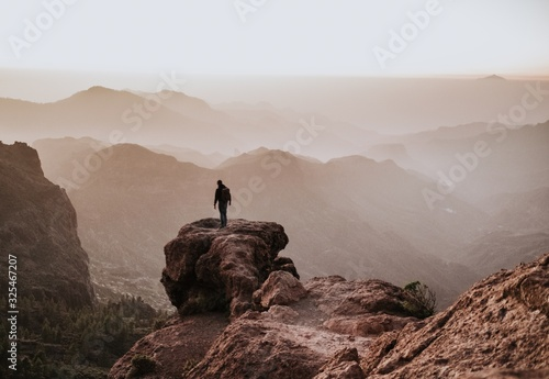 Obraz Behind shot of a man with a backpack standing on top of a cliff and enjoying the view - fototapety do salonu