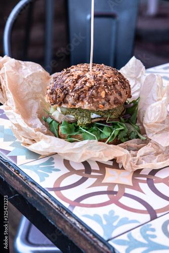 Świeżo grillowany burger leży na stoliku azelejos. Kanapka w amerykańskim stylu zawinięta w papier ekologiczn, street food. Restauracja w industrialnym stylu.