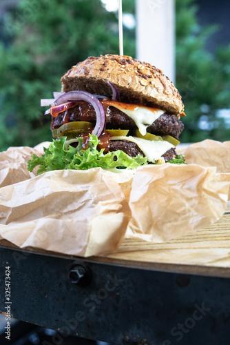 Burger na industrialnym stole w ekologicznym papierze. Duży lunch, burger meksykański grillowany na ogrodzie. Burger w bułce pełnoziarnistej.