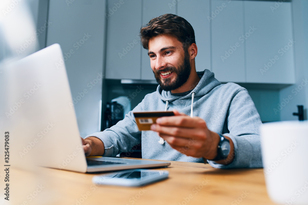 Fototapeta Cheerful young man paying bills online with credit card and laptop