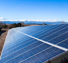 Looking Down A Long Solar Panel In Colorado With Mountains On The Horizon.