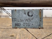 Closeup Of A No Trespassing And Fishing Sign Hung On An Old Farm Fence.