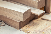 Oak Wooden Bar Blocks Materials Stacked At Carpentry Woodwork Workshop With Tools And Sawdust On Background. Timber Wood Blanks At Diy Workbench. Close-up Lumber Beam Details. Handcraft Hobby
