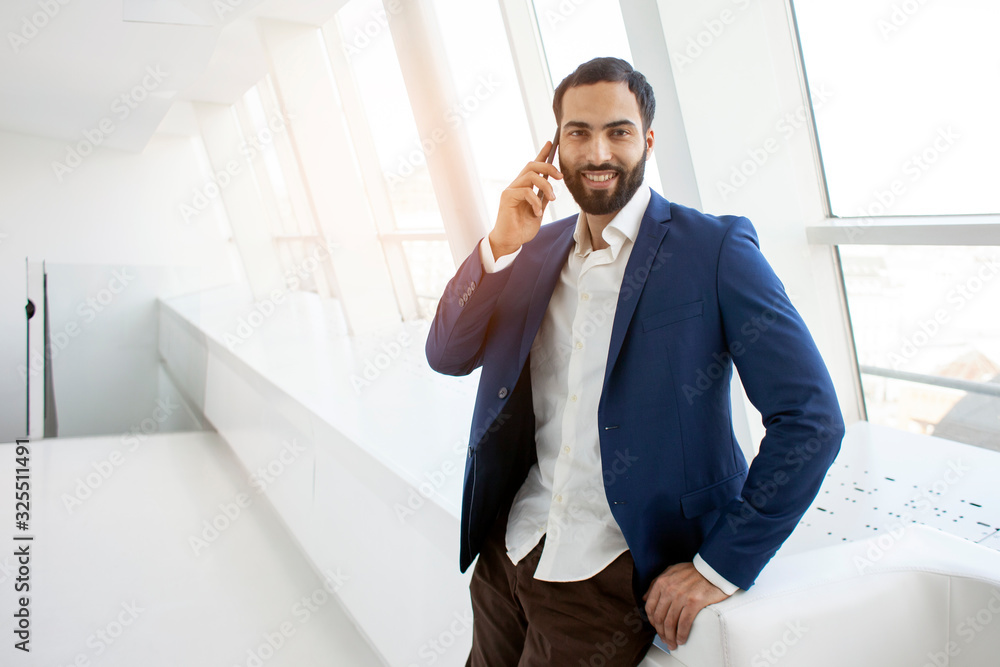 Fototapeta attractive successful businessman in a suit talking on the phone in a white office and looking out the window
