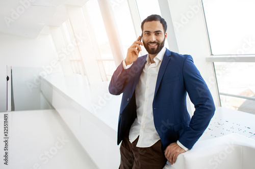 Fototapety, obrazy: attractive successful businessman in a suit talking on the phone in a white office and looking out the window