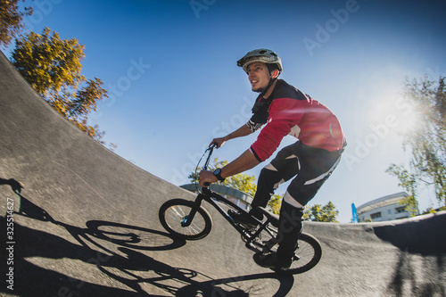 A young male riding a BMX bike through a berm while enjoying a sunny day Wallpaper Mural