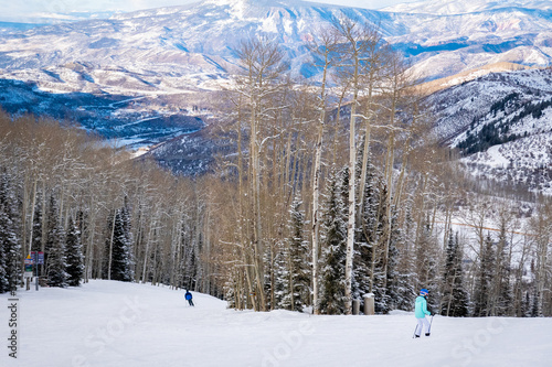 Scenic panoramic view as two skiers descend the slopes of the Aspen Snomass ski resort, in the Rocky Mountains of Colorado.