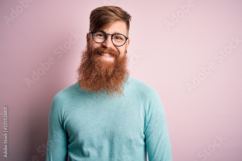 Fototapeta Handsome Irish redhead man with beard wearing glasses over pink isolated background with a happy and cool smile on face. Lucky person. obraz