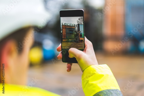 Obraz Architect holding a smartphone on construction site - young construction worker is using mobile phone on site - Construction worker with building plans and cellphone - Focus on mobile. warm filter - fototapety do salonu