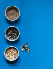 Three White Bowls With Sunflower Seeds, Pumpkin Seeds And Raw Sunflower Seeds On A Blue Background On Top