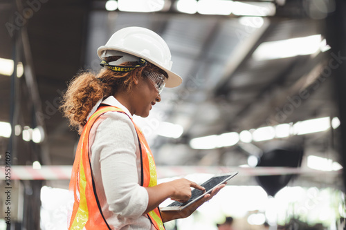 Close up hand industrial industrial plant with a tablet in hand,  Engineer looking of working at industrial machinery setup in factory Wallpaper Mural