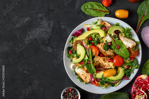 Fototapeta Grilled chicken breast and avocado salad with mixed greens, tomatoes and pomegranate in a plate on dark background obraz