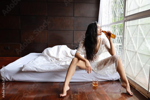 drunken asian woman in white lingerie, drinking and holding bottle of liquor alc Fototapet