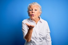 Senior Beautiful Woman Wearing Elegant Shirt Standing Over Isolated Blue Background Looking At The Camera Blowing A Kiss With Hand On Air Being Lovely And Sexy. Love Expression.