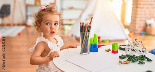 Photo Beautiful caucasian infant playing with toys at colorful playroom