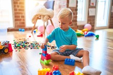 Young Caucasian Kid Playing At Kindergarten With Toys. Preschooler Boy Happy At Playroom.