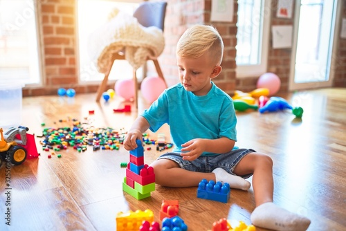 Tela Young caucasian kid playing at kindergarten with toys