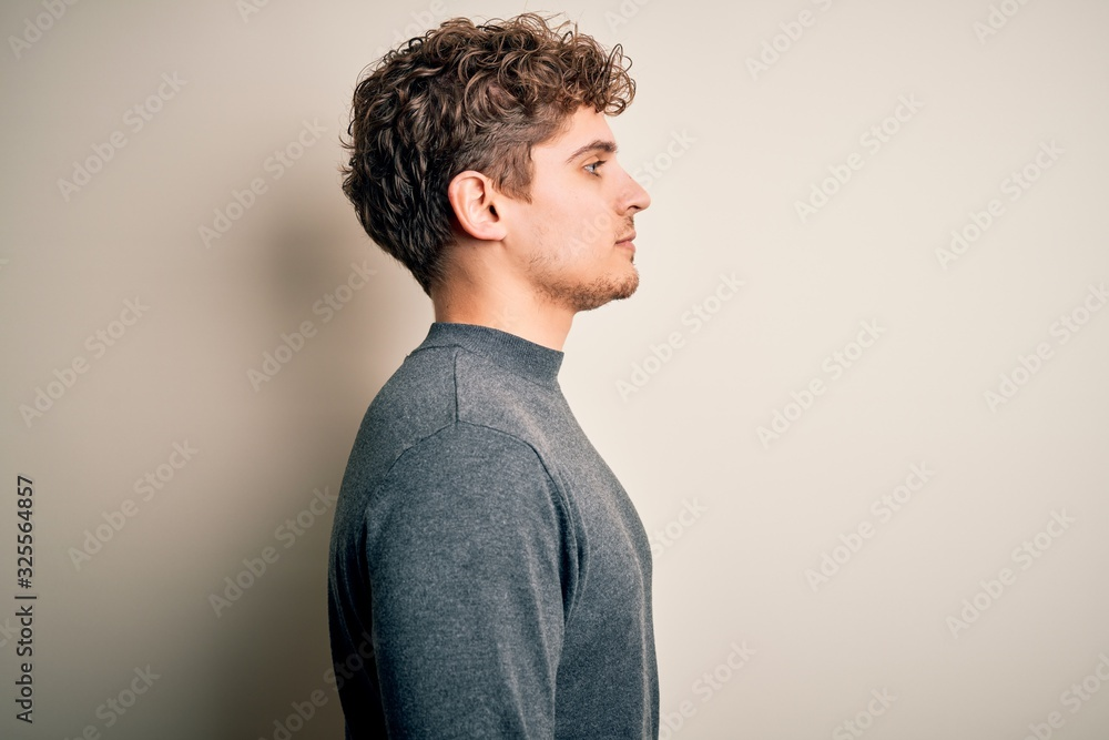 Fototapeta Young blond handsome man with curly hair wearing casual sweater over white background looking to side, relax profile pose with natural face with confident smile.