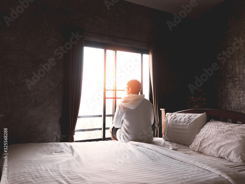 Back view of young man sitting alone on bed and looking through the window in bedroom