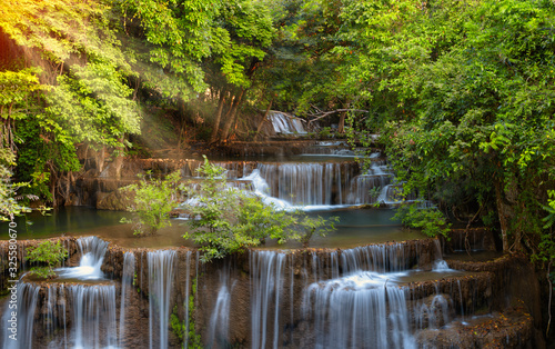 Obraz na ścianę wodospad   scenic-morning-sunrise-coming-through-the-trees-with-beautiful-waterfall-in-deep-forest-of