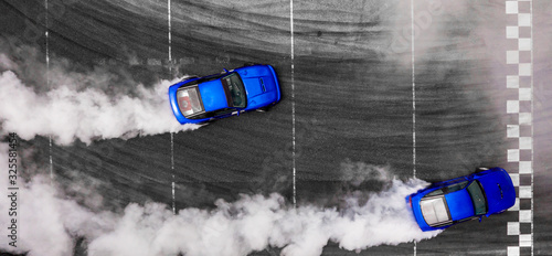 Valokuva Aerial top view two cars drifting battle on asphalt race track with lots of smoke from burning tires, Two race cars competition drift battle,  Race drift car with lots of smoke
