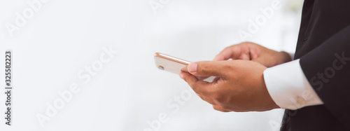 Close-up of hands using smartphone and typing message to assign jobs to employees Canvas Print