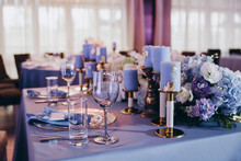 The Festive Table At The Wedding Party Is Decorated With Flower Arrangements, On The Table Are Plates With Napkins, Glasses, Candles, Cutlery