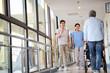 asian employee greeting residents in hallway of nursing home