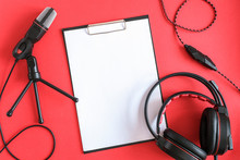 Headphones, Microphone And Clipboard With White Paper On Red Background. Concept Music Or Podcast. Top View, Flat Lay Copy Space Mockup For Your Text