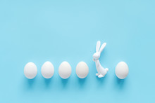 Row White Eggs And Bunny Rabbit Figurine On Blue Background With Copy Space. Happy Easter, Not Like Everyone Else Concept. Creative Flat Lay Top View. Template For Greeting Card, Invitation, Postcard