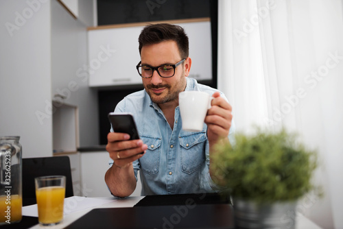 Fototapeta Handsome man having cup of coffee at home in the morning obraz
