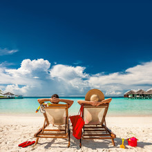 Couple In Loungers On Beach At...
