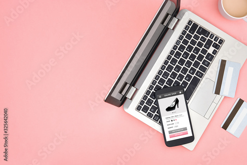 Photo Online store for women on smart phone screen over pink background with laptop, credit cards and copy space