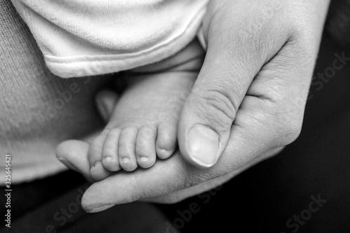 Photo Main d'une mère qui tient le pied de son bébé