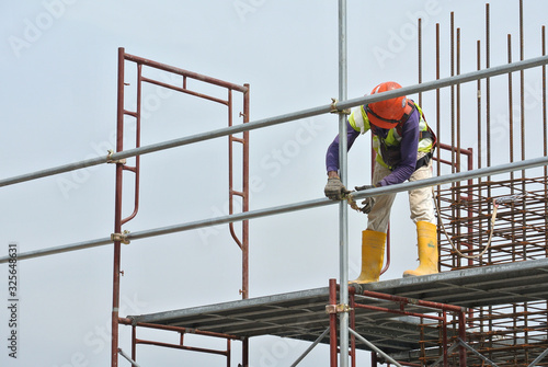 Construction workers wearing safety harness and installing scaffolding at high level in the construction site Wallpaper Mural